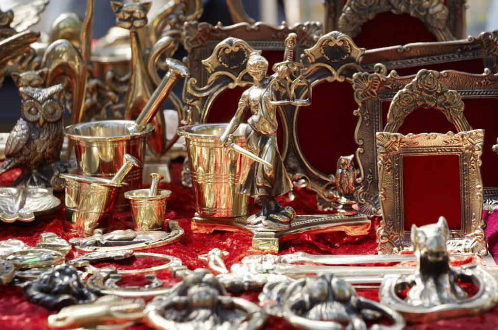 Assortment of brass statuettes frames ans other souvenirs.